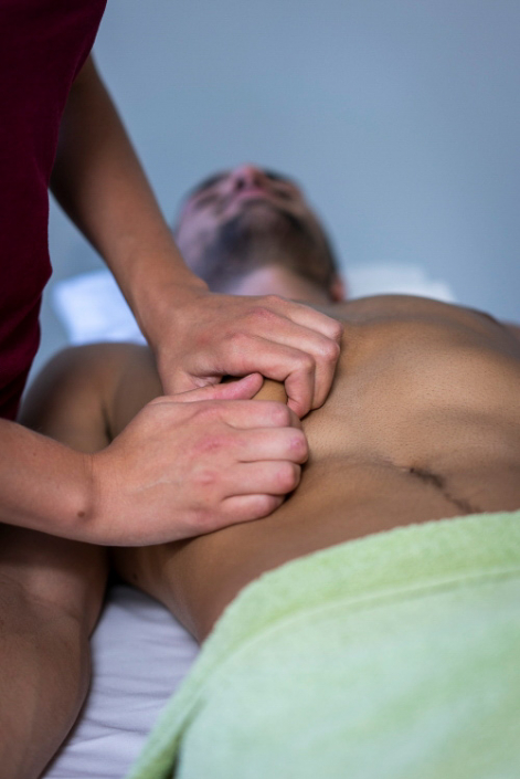 Faszien Lockerung bei jungen Mann mit verspannten Muskeln.