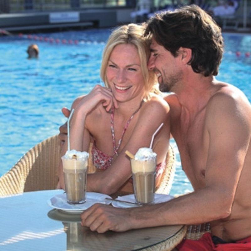 Ein verliebtes, attraktives Paar gönnt sich eine gemeinsame Cappuccino Auszeit im Außenbereich.