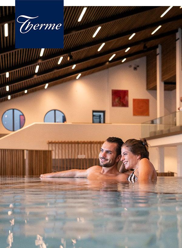 Junges Paar entspannt im Whirlpool in der großen Badehalle.
