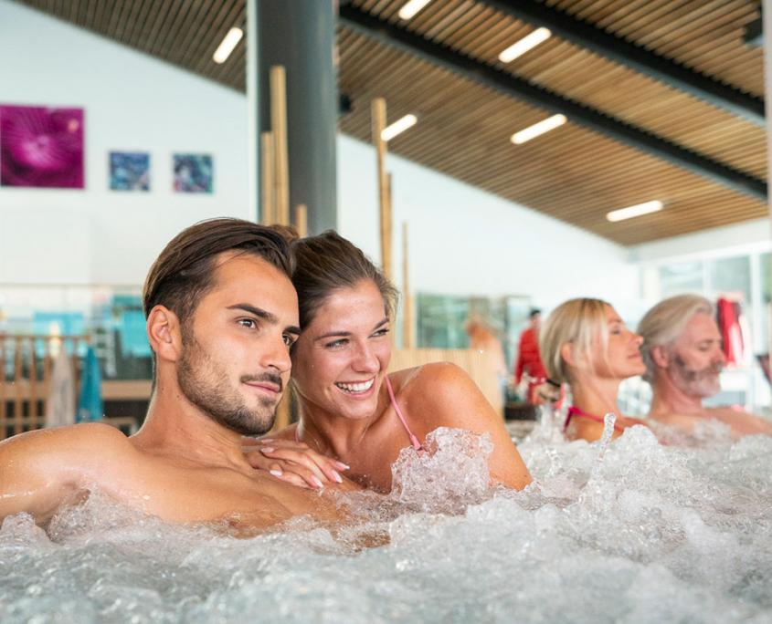 Ein junges Paar genießt die Auszeit im Whirlpool in der große Badehalle