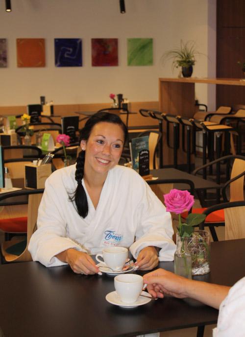 Junge Frau genießt einen Cappuccino auf einem mit einer pinken Rose dekorierten Tisch