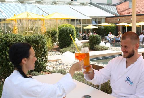 Ein junges Pärchen gönnt sich einen Drink auf der Sonnenterrasse der Wohlfühl-Therme