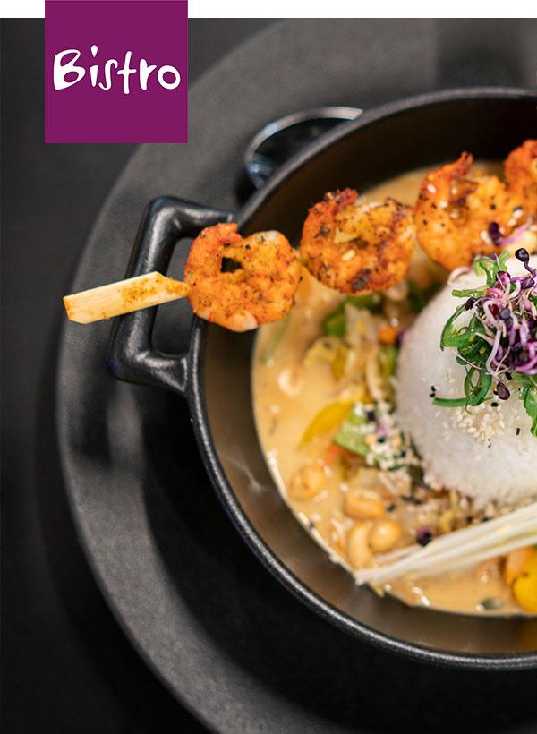 Asiatischer Duftreis mit kross gebratenen Garnelenspießen und Gemüse.