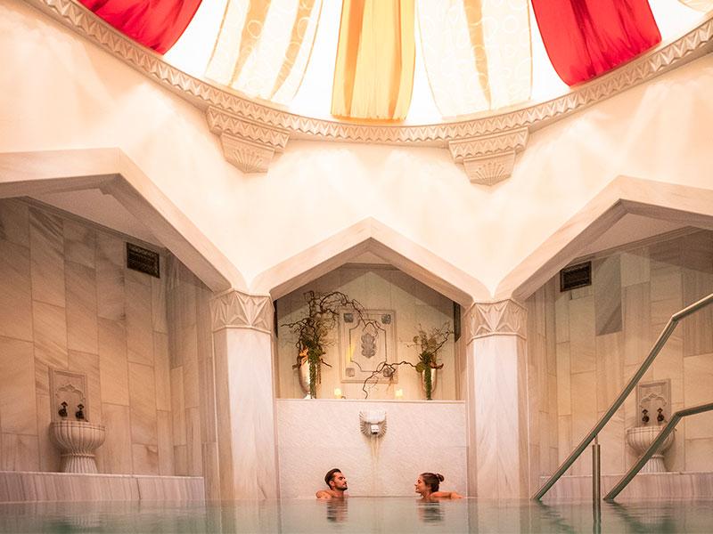 Ein junges Paar genießt ein Bad im Entspannungsbecken des Hamams unter einem gespannten Baldachin