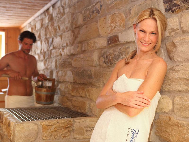Junge, an der Wand lehnende Frau, genießt Aufguss in der 95°C Sauna