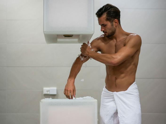 Ein muskulöser junger Mann reibt sich mit Eis aus dem Eisbrunnen ab.