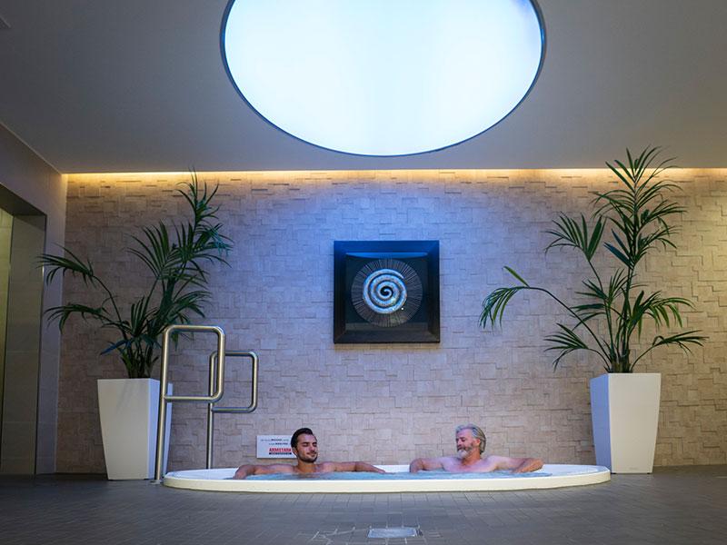 Zwei Männer baden im Innen-Whirlpool der SaunaPur unter einem blauen Farbwechsel