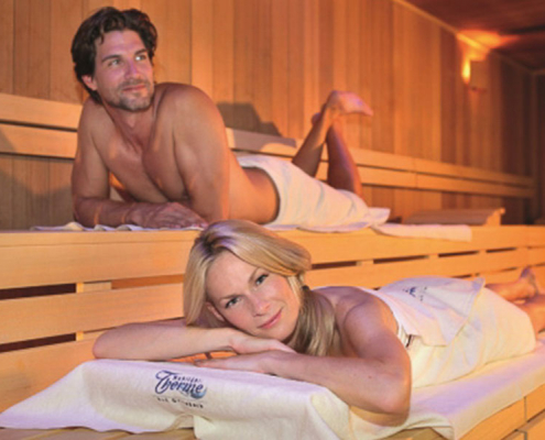 Paar genießt Sauna mit warmer Holzverkleidung
