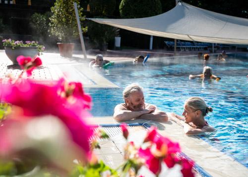 Ein älteres Paar genießt das Poolnudelbecken und erfreut sich an den Blumen